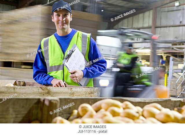 Portrait confident worker with clipboard at bin of fresh harvested potatoes
