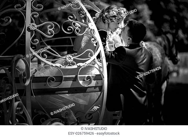 Romantic fairy-tale wedding couple bride and groom hugging in magical cinderella white carriage b&w