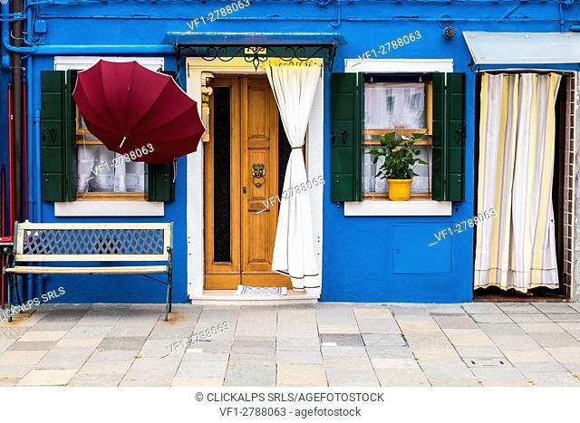 Burano, Venice, Veneto, North East Italy, Europe. Umbrella in front of colored facade in Burano