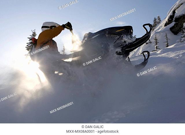 Man on snowmobile in deep powder, Whistler, British Columbia, Canada