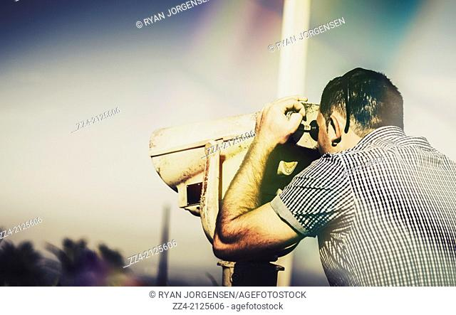 Sightseeing male tourist looking through telescope at mountain top lookout. Sky copyspace