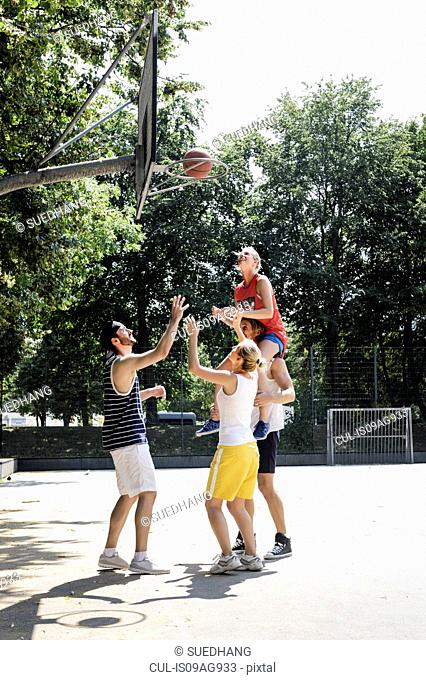 Group of friends having fun playing basketball
