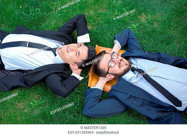 The two happy young businessmen in a suites lying on the green grass, top view. The one man is European, other is Chinese
