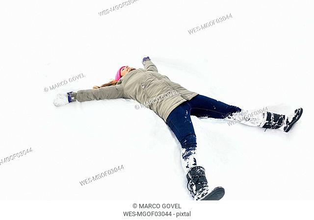 Young woman making a snow angel