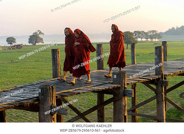 Buddhist monks walking on U Bein Bridge (built around 1850 and is believed to be the oldest and longest teakwood bridge in the world) spanning Taungthaman Lake...