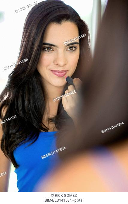 Hispanic woman applying lipstick in mirror