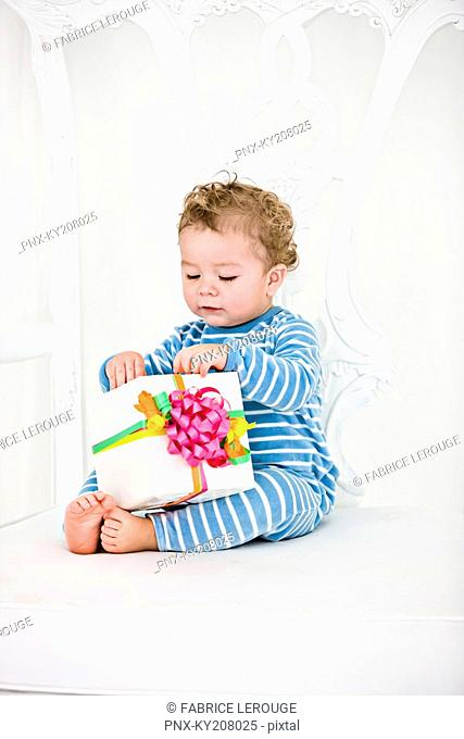 Baby boy playing with a present in an armchair