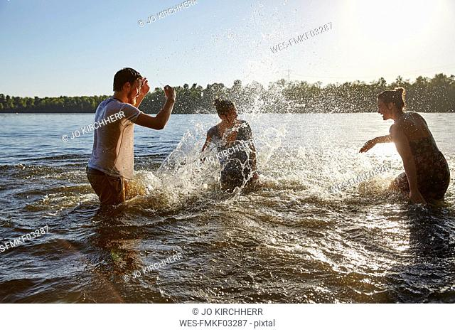 Playful friends splashing in a lake
