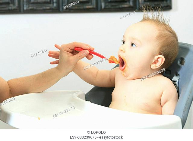 A Mother feeding hungry six month old baby solid food