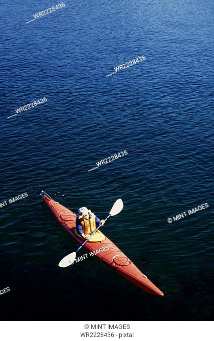 A man in a sea kayak on the calm waters off the coast of Southeast Alaska