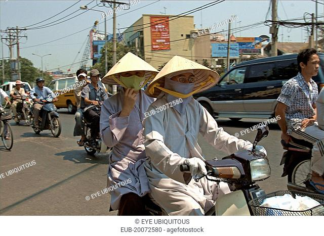 Monks in conical hats riding a a motorbike