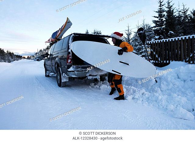 Kayak surfer loading a truck with gear, Homer, Southcentral Alaska, USA