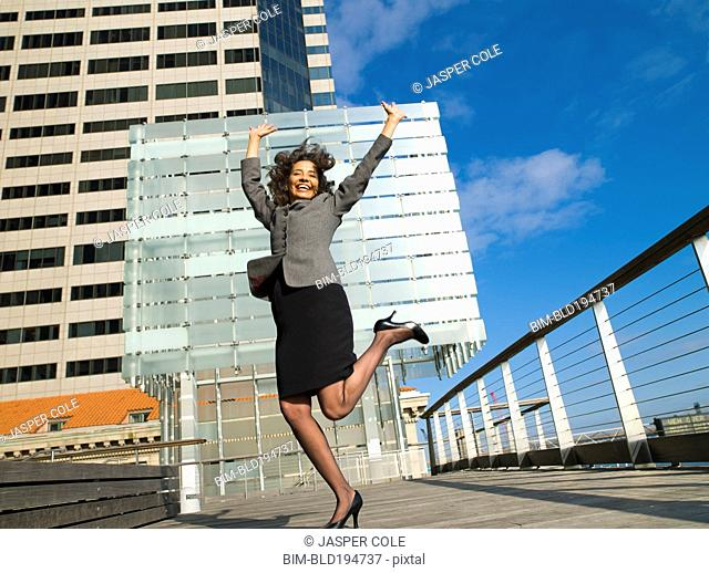 Excited Caucasian Businesswoman standing on one leg in city