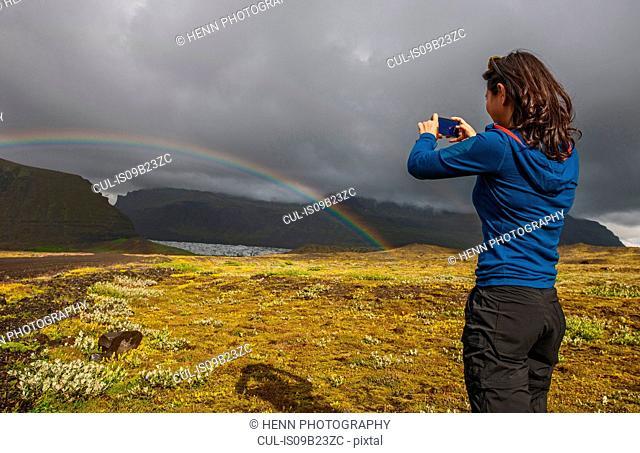 Woman photographing rainbow using smartphone, Svinafellsjokull, Skaftafell, Iceland