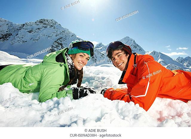 Couple lying in snow, Kuhtai, Austria