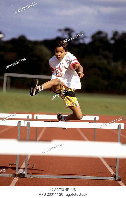 Boy jumping over hurdles on track