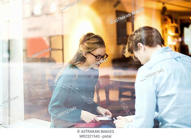Businessman and businesswoman discussing by office window