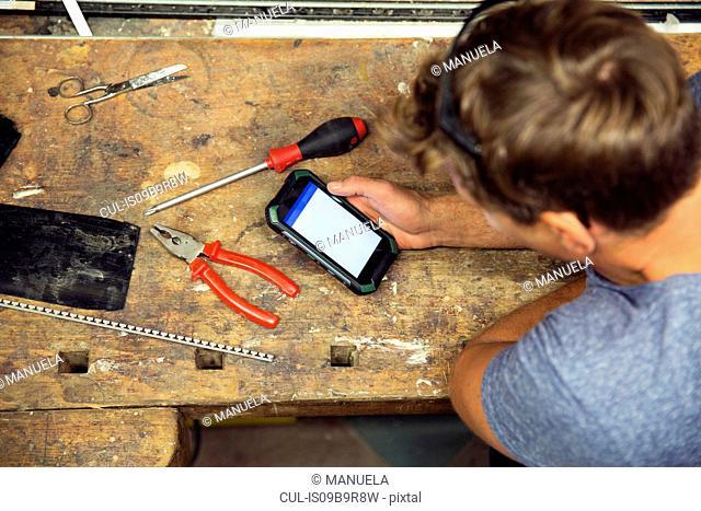 Man in workshop, using smartphone, overhead view