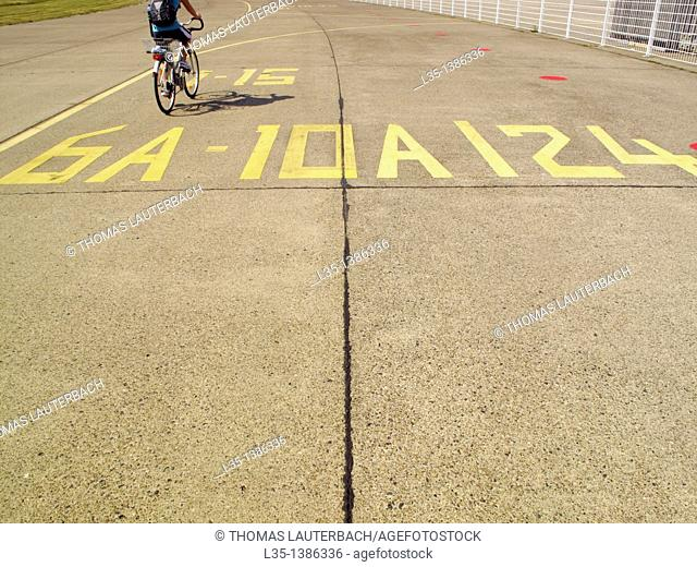 Man drives his bicycle on a taxi way of the old Berlin Tempelhof airport, Germany