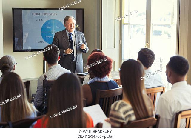 Businessman leading conference presentation at television screen