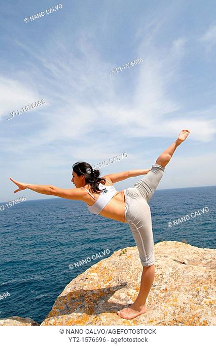 Young brunette woman doing yoga and stretching in nature