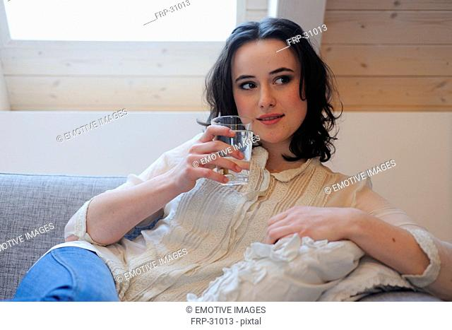 Young woman on couch drinking glass of water