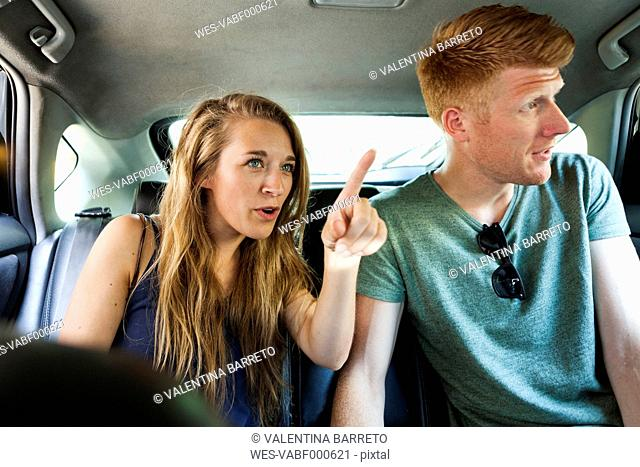 Couple sitting in taxi looking through window