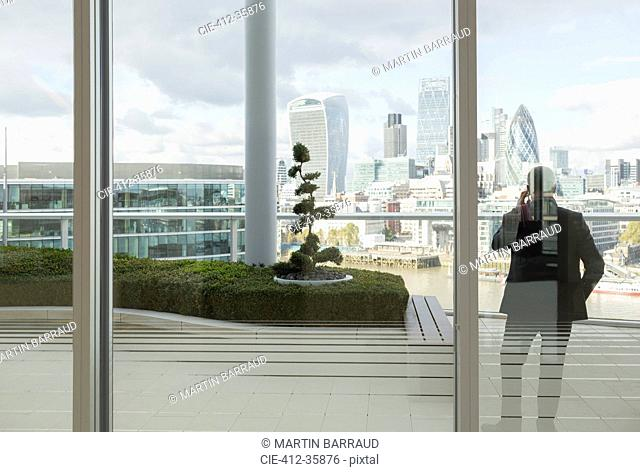 Businessman talking on cell phone on balcony with urban city view, London, UK