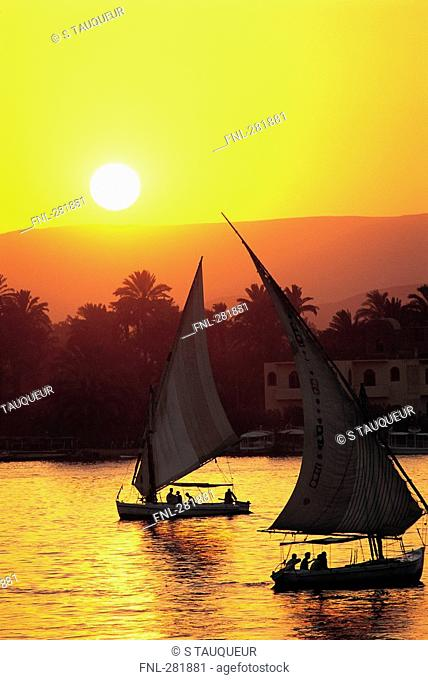 Silhouette of two sailboats in river at dusk, Luxor, Egypt