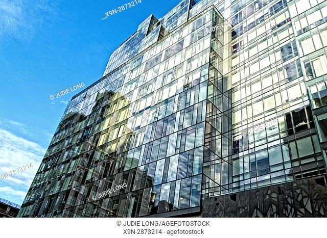 New York City, Manhattan. Looking Up at Late Day Reflections in a Glass Walled Mixed Use Building