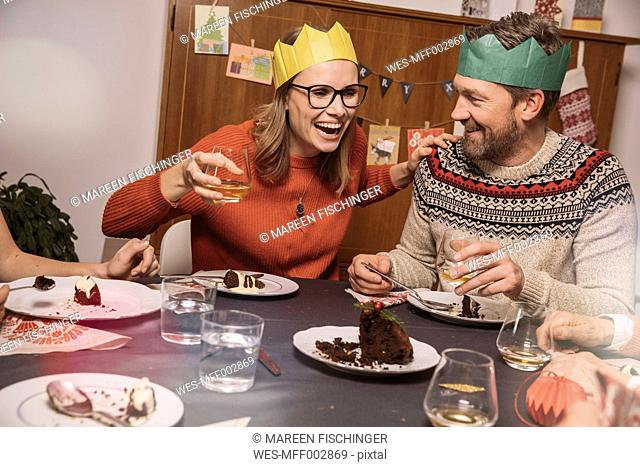 Happy couple with paper crowns laughing while having Christmas dinner