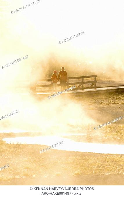 A mother and daughter visiting the West Thumb Geyser Basin, Yellowstone National Park, Wyoming, USA