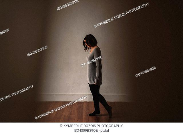 Woman pacing in front of grey wall