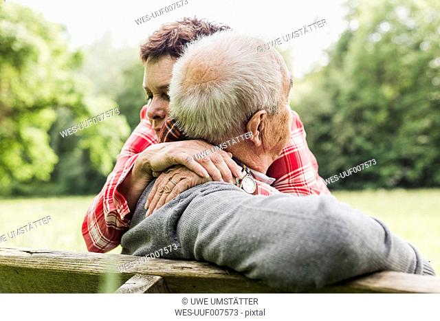 Happy woman hugging her old father sitting on a bench in nature