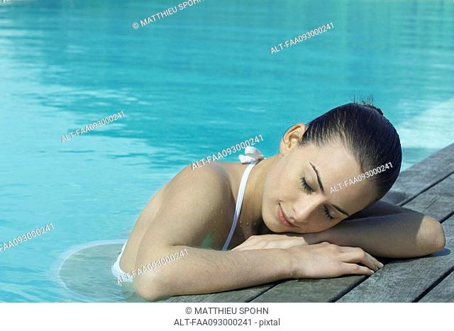 Woman in pool leaning against deck, resting head on arms