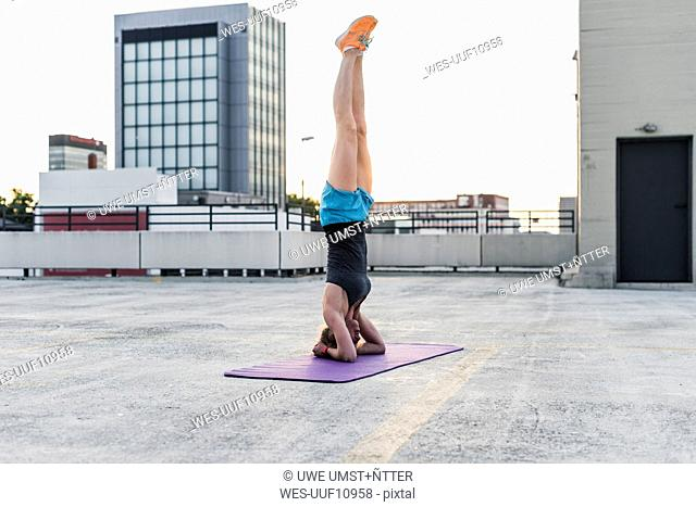 Woman doing a headstand on parking level in the city