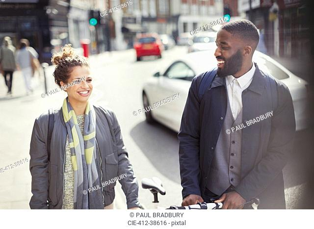Smiling couple commuting with bicycle on sunny urban street