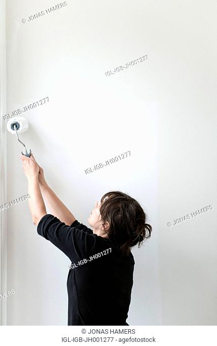 Woman standing in front of a wall as she is busy painting with a paint roller