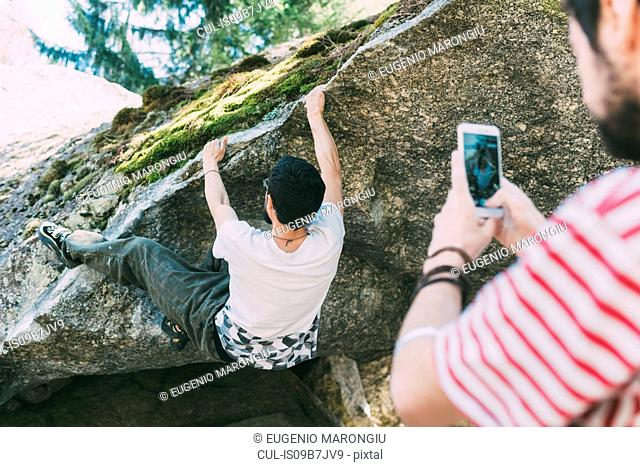 Male boulderer photographing friend with smartphone, Lombardy, Italy