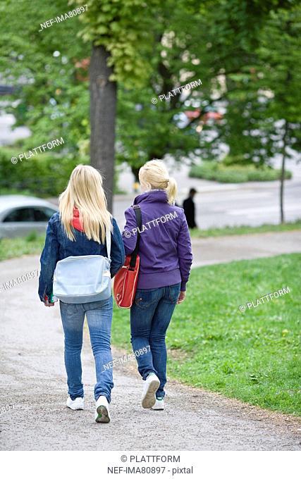 Rear view of two teenage girls walking through park