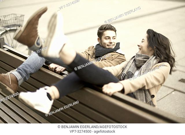 young smiling teenage couple sitting on bench the wrong way round in city, hanging out together, legs up, upside down, in Cottbus, Brandenburg, Germany