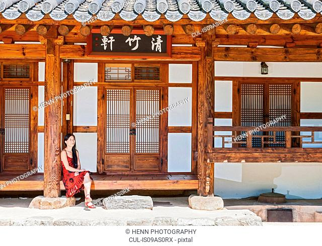 Woman sitting in front of traditional house at Damyang cultural village, South Korea