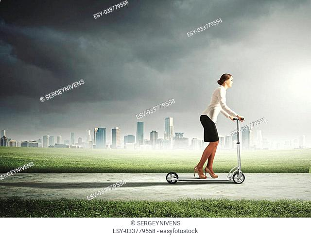 Image of attractive businesswoman riding a scooter