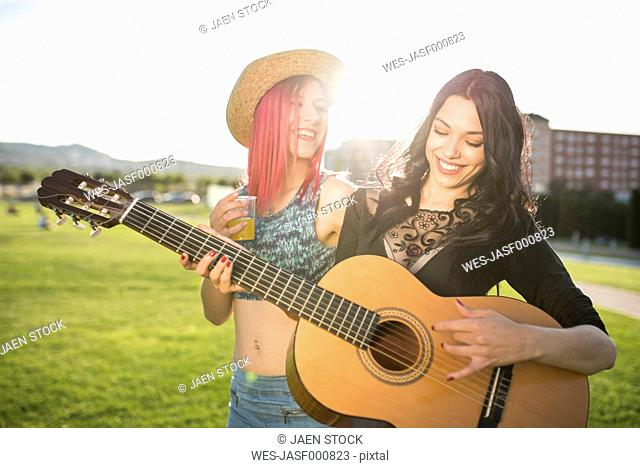 Young women having a drink, playing guitar