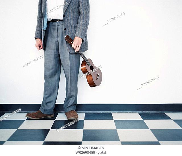 A man in a grey suit holding a ukulele