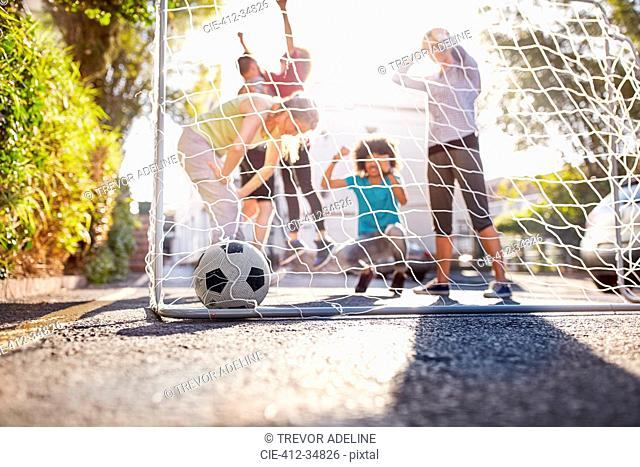 Friends playing soccer on sunny urban summer street