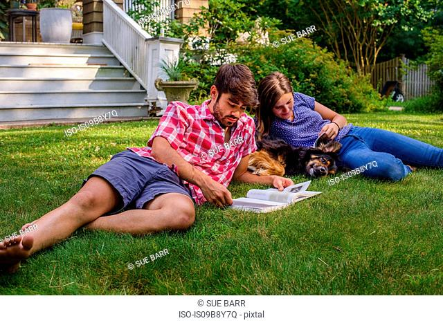 Couple on grass in garden with dog, reading