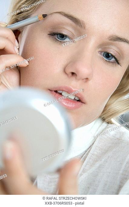 woman applying eyebrow liner