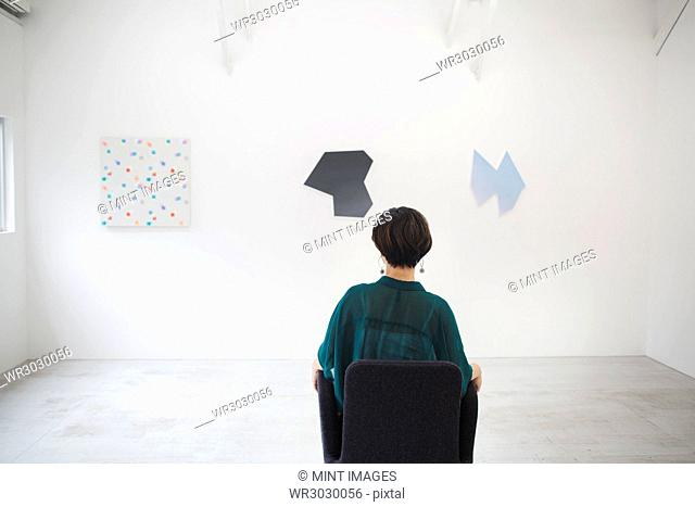 Rear view of woman with short black hair wearing green shirt sitting in art gallery, looking at modern paintings