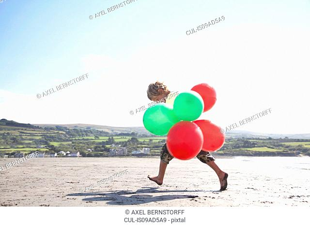 Boy on beach holding balloons, Wales, UK